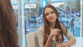 Två skolflickaflickvänner som dricker coctailar och talar i ett kafé I bakgrundssikten av en stadsgata Höst arkivfilmer
