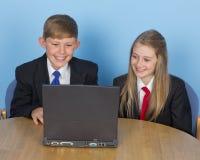 Två skolungdom, genom att använda en dator hemma arkivfoton