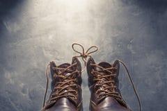 Två skor med snör åt bundet på bakgrund av betongväggen arkivfoto