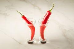 två skott av skottet vodka och röd peppar/två av vodka och röd pepp arkivbild