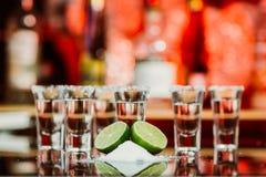 Två skott av tequila med limefrukt och saltar på en trätabellstång på bakgrunden av ljusa ljus av stången royaltyfria foton