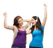 Två skratta flickor med att dansa för hörlurar Royaltyfria Bilder
