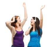Två skratta flickor med att dansa för hörlurar Royaltyfria Foton