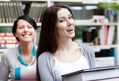 Två skratta flickvänner bär böcker royaltyfria foton