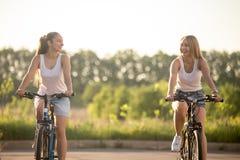 Två skratta unga kvinnor som kör cyklar royaltyfri foto