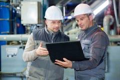 Två skyddande linje arbetare i fabrik fotografering för bildbyråer