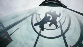 Två skydivers flyger in i vindtunnelen Extrem hoppa med fritt fall tandemcykel i vindtunnel stock video