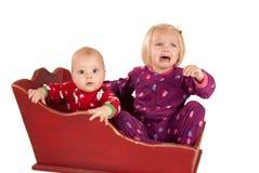 Två små barn i släde en är ledsna och gråt Arkivbilder