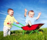 Två små barn som tillsammans utomhus spelar Royaltyfri Bild