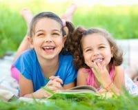 Två små flickor är läseboken royaltyfri foto