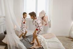 Två små flickor i deras pyjamas har gyckel som hoppar på en säng i ett solbelyst hemtrevligt sovrum arkivbild