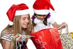 Två små flickor i päls-lock med shoppingpåsar Jul royaltyfri foto
