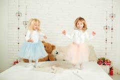 Två små flickor i trevliga klänningar i rolig banhoppning på en säng royaltyfri foto