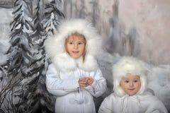 Två små flickor i vita lag och vita pälshattar Royaltyfri Bild