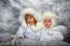 Två små flickor i vita lag och vita pälshattar Royaltyfri Fotografi