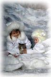 Två små flickor i vita lag och vita pälshattar Arkivbild