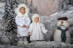 Två små flickor i vita lag och vita pälshattar Arkivfoton