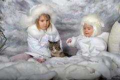 Två små flickor i vita lag och vita pälshattar Royaltyfria Bilder