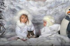 Två små flickor i vita lag och vita pälshattar Arkivfoto