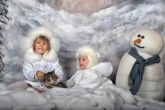 Två små flickor i vita lag och vita pälshattar Royaltyfri Foto