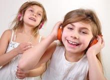 Två små flickor med hörlurar som lyssnar till musik arkivbild