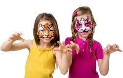 Två små flickor med målade framsidor som brummar som djur Arkivbild
