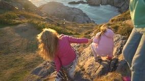 Två små flickor och deras mamma går på en stenig nordlig kust stock video