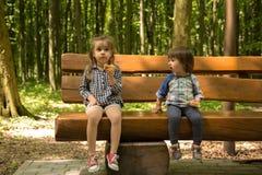 Två små flickor sitter på bänken Fotografering för Bildbyråer
