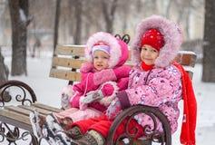 Två små flickor sitter på en shoppa i vintern parkerar Royaltyfria Bilder