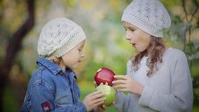 Två små flickor som äter röda och gröna äpplen i blomma, parkerar stock video