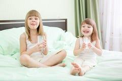 Två små flickor som dricker mejeri på säng Royaltyfri Foto