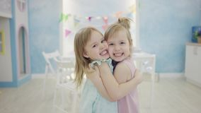 Två små flickor som kramar sig som framme står av kameran lager videofilmer