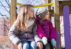 Två små flickor som poserar på lekplatsen Arkivbild