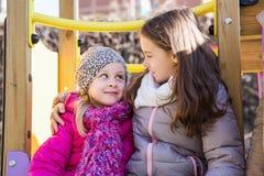 Två små flickor som poserar på lekplatsen Arkivbilder