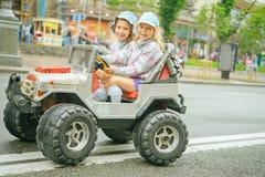 Två små flickor som rider leksakbilen Arkivfoto