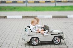 Två små flickor som rider leksakbilen på gator av staden royaltyfria foton