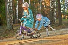 Två små flickor som rider leksakcirkuleringen Royaltyfri Foto