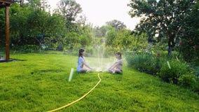 Två små flickor som sitter på grön gräsmatta nära den arbetande trädgårdspridaren lager videofilmer