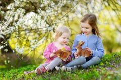 Två små flickor som spelar i en trädgård på påsk Fotografering för Bildbyråer