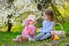 Två små flickor som spelar i en trädgård på påsk Arkivbild