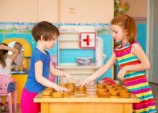 Två små flickor som spelar i kontrollörer på dagiset arkivbilder