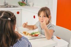 Två små flickor som tycker om en läcker mat Arkivbild