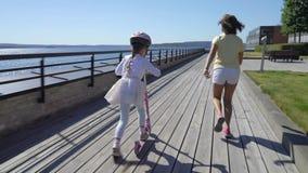 Två små flickor som utomhus rider sparksparkcykeln lager videofilmer