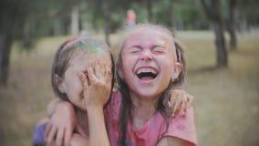 Två små flickor suddiga med kulört vatten för det pulverHoli stänket i sommaren parkerar arkivfilmer