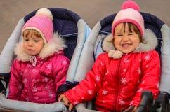 Två små flickor, systrar En gråter, andra skratt arkivbild