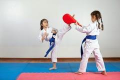 Två små flickor visar kampsporter som tillsammans arbetar Royaltyfria Bilder