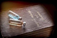 Två små medicinflaskor av medicin på en forntida bok av anatomi av nervsystemet Royaltyfri Fotografi
