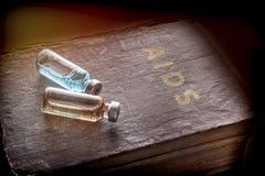 Två små medicinflaskor med medicin på en gammal bok av HJÄLPMEDEL Arkivbild