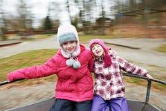 Två små skratta ungeflickor på carrouselen Arkivbild