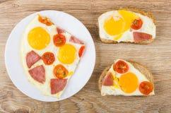 Två smörgåsar med det stekte ägget, korven, tomater och det stekte ägget Arkivbilder